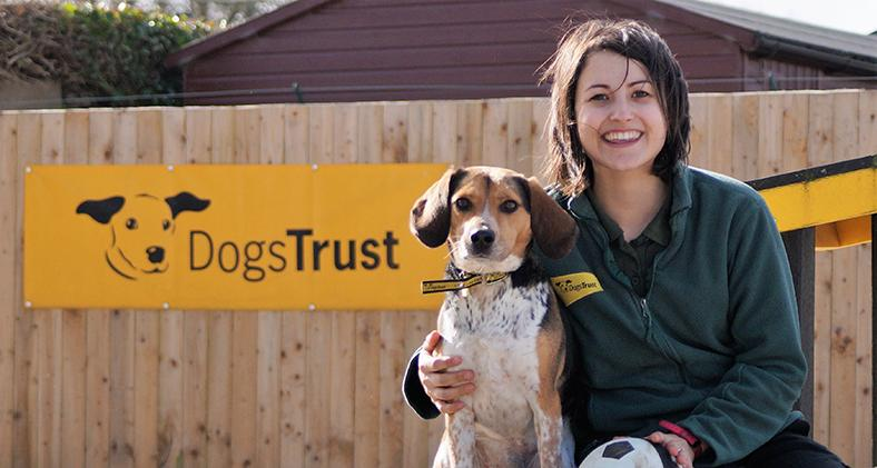 Dogs Trust staff member outside with a dog